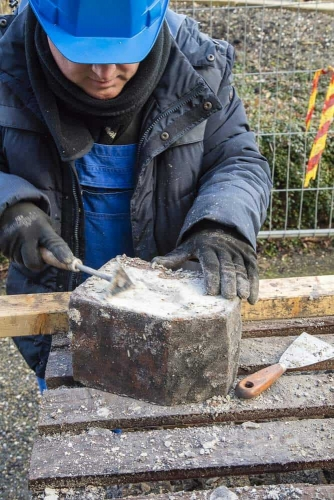 De hele stenen worden door vrijwilligers kaal geschrapt.