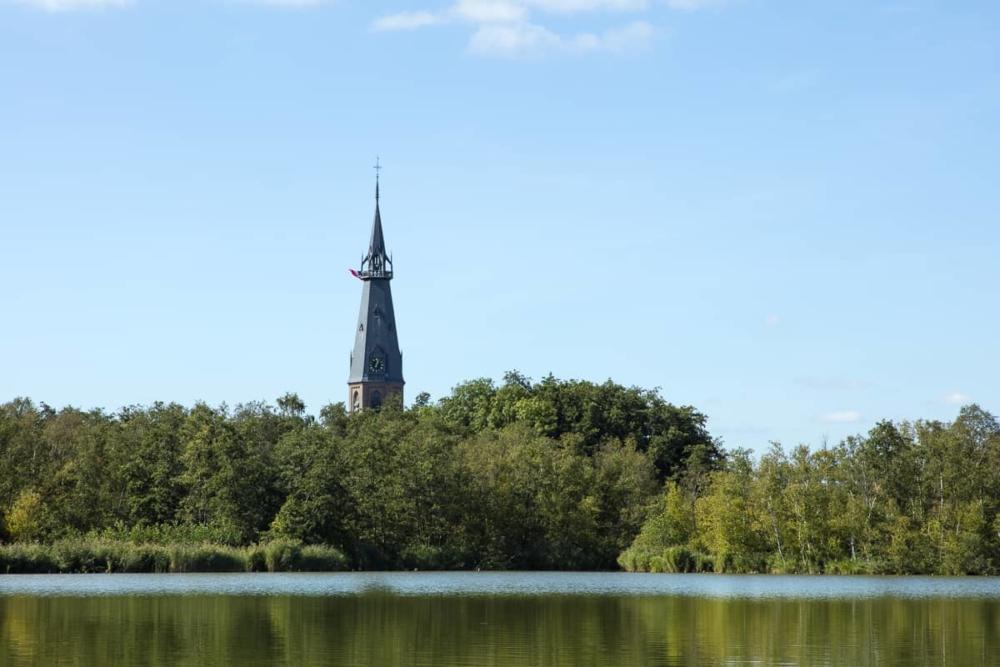 Rondvaart op de Amstelveense Poel - St. Urbanus toren met vlag